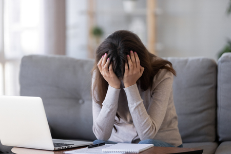 Upset millennial woman in panic holding head in hands frustrated shocked sitting in front on laptop on couch at home, tired bored student feel exhausted fatigued depressed having problem or headache