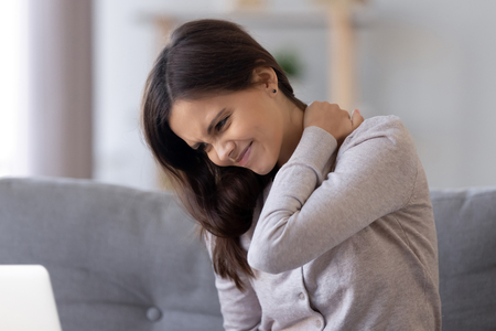 Steifes Nackenkonzept, junge Frau, die sich unwohl fühlt, verletzte Gelenkschmerzen, reibt verspannte Muskeln, müdes Teenager-Mädchen massiert sich zurück, um Fibromyalgieschmerzen nach langem Computerstudium in falscher Haltung zu lindern post