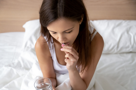 Young woman takes sleeping morning after pill sits on bed suffers from insomnia headache, ill sick millennial girl feels unwell holding medicine painkiller for flu prevention, emergency contraception Stok Fotoğraf