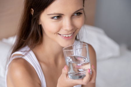 Thirsty young woman holding glass drinking pure mineral water in early morning for body health, happy millennial girl feels dehydrated after waking up in bed, healthy lifestyle and hydration concept