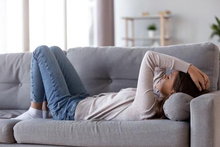 Traurige depressive junge Frau, die zu Hause auf der Couch liegt und Kopfschmerzen Müdigkeit Einsamkeit verspürt, verärgertes, krankes, krankes Teenager-Mädchen leidet unter Migräne-Angst, schläfrig schläfriger Teenager ruht sich nach Stress auf dem Sofa aus