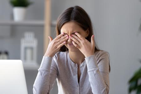 Chica adolescente cansada frotándose los ojos secos e irritables siente tensión ocular tensión migraña después del trabajo en la computadora, estudiante trabajadora joven agotada que alivia el dolor de cabeza, mala visión borrosa débil, problema de la vista