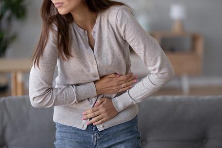 Magenschmerzen-Konzept, junge kranke Frau, die den Bauch hält und unter Magenschmerzen leidet und schmerzhafte Beschwerden fühlt