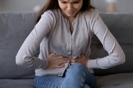 Mujer joven enferma con dolor sosteniendo el estómago estómago sintiendo dolor de abdomen dolor de estómago síntomas de pancreatitis o diarrea, malestar adolescente que sufre de indigestión flatulencia concepto de problema abdominal Foto de archivo