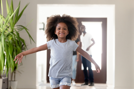 Cute carefree kid girl running in luxury house hallway on moving day, funny excited african child exploring new modern home looking at camera, happy black family buy real estate concept, portrait Standard-Bild