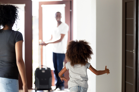 Happy child daughter running to meet african dad coming home with suitcase, rear view at little kid girl hurrying to hug father arriving after business trip, welcome back daddy, black family reunion 스톡 콘텐츠