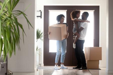 Felice famiglia nera con bambina che tiene la scatola che entra in casa il giorno del trasloco, genitori afroamericani e bambino in piedi nel corridoio, mutuo, trasferimento, inquilini benvenuti nel nuovo concetto di casa