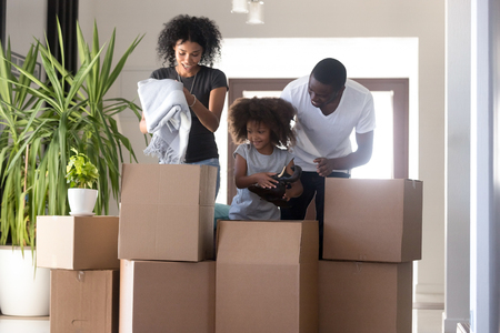 African american family having fun unpacking boxes with kid helping parents packing together at home, black parents and mixed race child daughter preparing for relocation or moving in new house