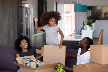 Happy child girl jump out of box play with parents in living room, excited joyful african family and kid daughter laugh having fun packing unpacking boxes, black family moving in new home relocation