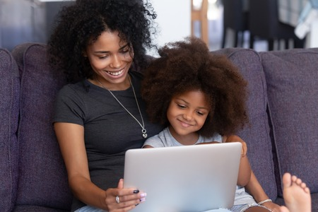 Smiling african american mother and kid daughter having fun with computer sitting on couch, happy mixed race mom with child girl using laptop, watching cartoons, making video call, doing shopping