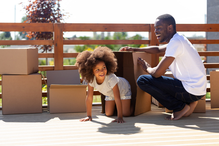 Happy african dad and cute kid girl laughing playing with boxes on porch outdoor on moving day, black father with little daughter have fun outside new house, daddy and funny child enjoy relocation Stock Photo