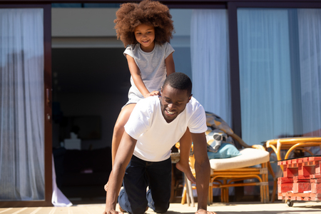 Happy black dad riding mixed race daughter on back outdoors, playful african father enjoying playing funny game with kid girl together outside house, daddy and child laughing having fun on porch