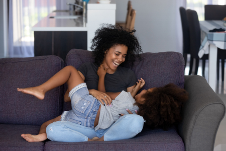 Happy african american mom tickling kid daughter laughing together on couch, cheerful black mother playing funny game with little cute girl at home, mixed race child having fun relaxing with mum