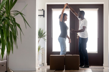 Happy african american first time home buyers couple dancing celebrating relocation or buying new house standing in hallway with boxes, excited black family tenants enjoy moving day, mortgage goals