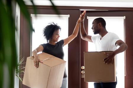 Los inquilinos de la feliz pareja de jóvenes afroamericanos dan cinco celebran el día de la mudanza en las cajas de la casa propia, la familia negra emocionada, los propietarios de los compradores por primera vez en la nueva casa, los objetivos de la hipoteca, el concepto de reubicación