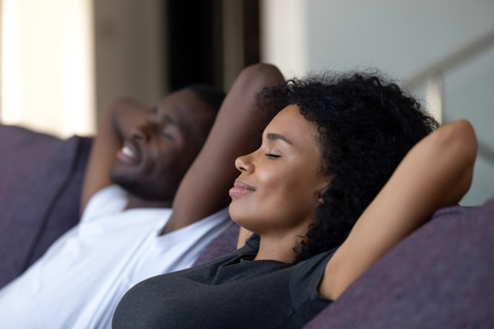 Relaxed african couple enjoying peaceful rest breathing fresh air at home on comfortable couch, happy lazy young black couple having nap leaning on sofa relaxing in living room feel no stress free Banco de Imagens - 116422847