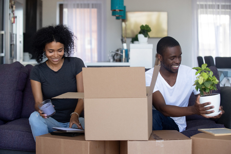 African american happy couple unpacking cardboard boxes in living room moving into new home, young black family packing stuff preparing for relocation or renovation in house or flat, removals concept Foto de archivo - 116422881