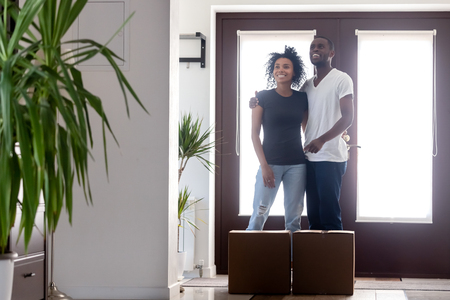 Moving day for millennial african couple concept, happy young black first time buyers home owners embracing standing in new modern luxury house hallway with boxes, family goals, mortgage, relocation 版權商用圖片