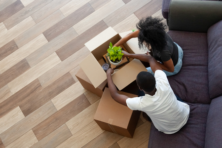 Black couple unpacking cardboard boxes in living room moving in out new home, african tenants renters packing stuff preparing for relocation house renovation, removals concept, top view from above Foto de archivo - 116422902