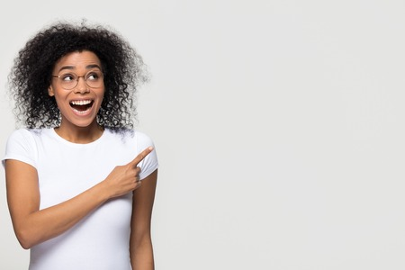 Excited african woman look up aside pointing finger at copy space amazed by unbelievable product service sale, surprised black lady indicate advertise cheap offer isolated on white studio background