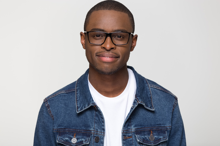 Confident young african american man wearing denim jacket and glasses looking at camera smiling, black handsome millennial smart male guy nerd isolated on blank grey white studio background, portrait 写真素材