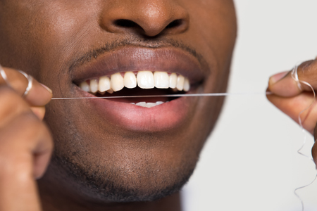 Close up view of african american black man cleaning white healthy teeth holding using dental floss isolated on grey studio blank background, oral hygiene concept, tooth health care caries prevention Foto de archivo - 116422952