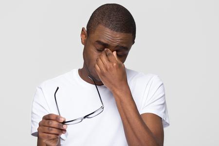 Hombre afroamericano cansado masajeando el puente de la nariz quitándose las gafas sintiendo fatiga ocular aislada sobre fondo gris blanco del estudio, joven negro que tiene dolor de cabeza, problema de visión seca e irritable Foto de archivo