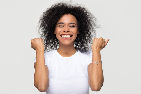 Excited happy young african american woman feeling overjoyed isolated at white grey studio background, lucky euphoric black girl winner celebrating win victory success raising hands in yes gesture Stok Fotoğraf