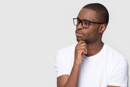 Thoughtful african man holding hand on chin looking at copy space feeling uncertain, doubtful black guy with unsure face thinking considering making decision isolated on white grey studio background