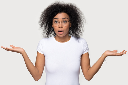 Confused doubtful shocked black woman shrugging feel baffled looking at camera isolated on white grey blank studio background, clueless african female puzzled stunned unaware about ambiguous problem Stock Photo