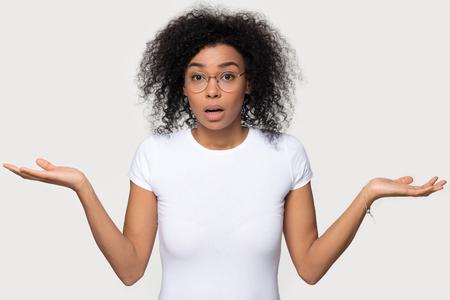 Verwirrte zweifelhafte schockierte schwarze Frau, die die Achseln zuckt, fühlt sich verwirrt, wenn sie die Kamera einzeln auf weißem grauem, leerem Studiohintergrund betrachtet, ahnungslose afrikanische Frau verwirrt, fassungslos, ohne sich des mehrdeutigen Problems bewusst Standard-Bild