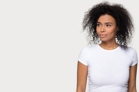 Young confident thoughtful dreamy african black woman standing isolated on white grey blank background with copyspace looking forward away thinking of future vision contemplating dream of leadership. Stok Fotoğraf
