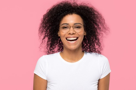 Cheerful funny young african american girl wearing optical glasses laughing isolated on pink blank studio background, happy black woman student in eyeglasses having fun looking at camera, portrait