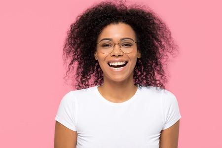 Fröhliches, lustiges junges afroamerikanisches Mädchen, das eine optische Brille trägt, die einzeln auf rosafarbenem leerem Studiohintergrund lacht, glückliche schwarze Studentin in Brillen, die Spaß beim Betrachten der Kamera hat, Porträt