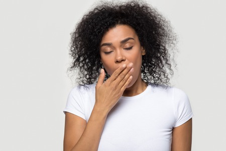 Tired funny drowsy african american woman yawning isolated on white grey studio background, sleepy inattentive deprived black female feeling somnolent lazy bored gaping suffering from lack of sleep Stock fotó