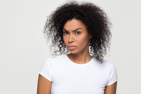Suspicious annoyed young african american woman with distrustful face looking at camera, skeptical sarcastic black girl feeling cautious dubious distrusting isolated on grey white studio background Stockfoto