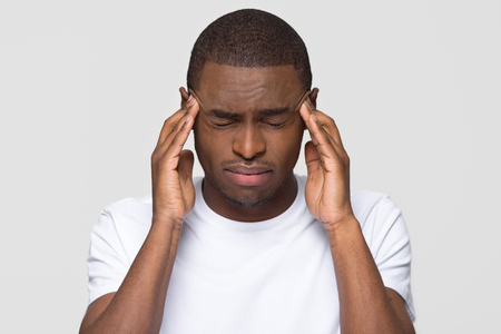 Stressed young african american man feel pain having terrible strong headache concept, tired upset black guy massaging temples suffering from migraine isolated on white grey studio blank background Reklamní fotografie