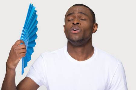 Sweaty african man suffering from heat stroke problem holding waving using fan isolated on white grey studio background, funny black guy sweating cooling himself feeling relief in summer hot weather