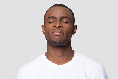 Calm mindful african american man enjoy taking deep breath of fresh air isolated on white studio background, happy black guy with serene face eyes closed meditating feeling harmony and no stress free
