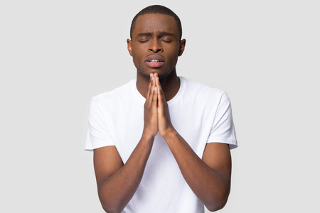 Worried young african american man put hands together ask for help forgiveness in prayer isolated on white studio background, religious christian black guy praying with hope, worship belief concept