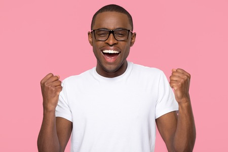 Excited overjoyed lucky black man feeling winner screaming with joy looking at camera isolated on pink studio background, african guy celebrating win triumph rejoicing victory motivated by success Stock fotó