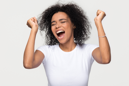 Overjoyed young african american woman screaming with joy celebrating victory win success isolated on blank grey white studio background, happy excited black girl rejoicing triumph feeling winner Stock Photo