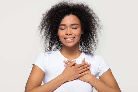 Une femme noire heureuse et pleine d'espoir se tenant la main sur la poitrine se sentant heureuse, une femme africaine sincère et reconnaissante exprimant un amour sincère appréciation gratitude honnêteté isolée sur fond de studio blanc Banque d'images