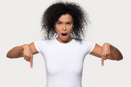 Shocked black woman looking at camera point fingers below indicate unbelievable sale offer, surprised african girl youtuber show down at subscription like button isolated on white studio background