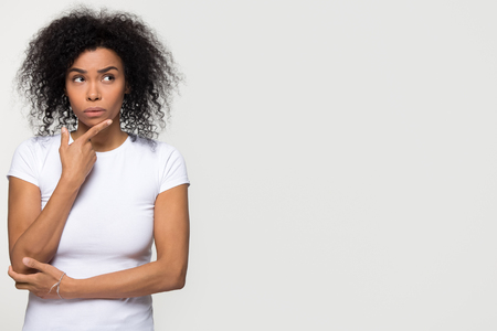 Thoughtful doubtful young african woman holding hand on chin looking at copy space aside, uncertain black lady feeling hesitation thinking choosing making decision isolated on white studio background