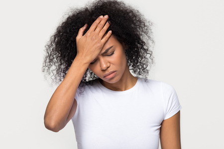 Upset young african woman touching forehead feeling headache hurt, sad ill black girl frustrated suffering from migraine fever, depressed about problem isolated on white grey studio blank background