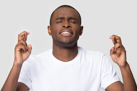 Hopeful young african american man crossing fingers wishing for good luck isolated on white blank studio background, funny superstitious black guy student hope for win believe in superstition concept