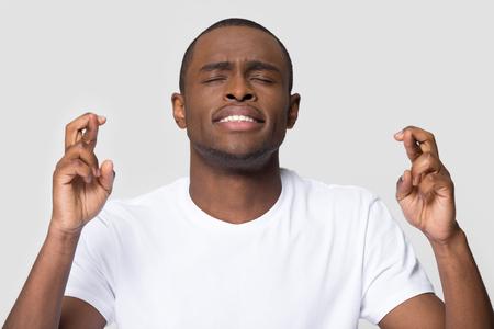 Speranzoso giovane uomo afroamericano incrociando le dita che desiderano buona fortuna isolato su sfondo bianco studio vuoto, divertente superstizioso ragazzo nero studente speranza per la vittoria crede nel concetto di superstizione