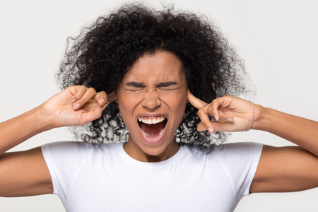 Stubborn angry annoyed black woman sticking plug fingers in ears not listening, mad african girl feel ear pain scream suffer from too loud noise sound isolated on white grey blank studio background 写真素材