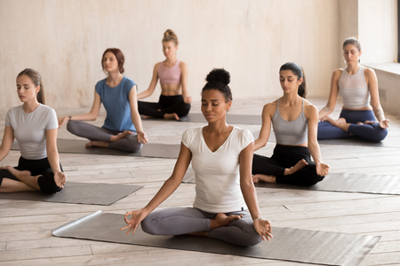 Diverse young female yogi working out sitting on rubber mats in lotus position, multiracial girls practice yoga poses with eyes closed in fitness studio, barefoot sportive women meditate together